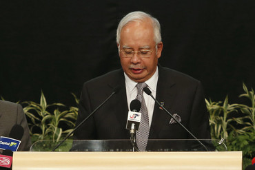 Malaysian Prime Minister Najib Razak reads the announcement (AAP)